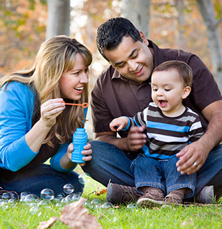 Parents blowing bubbles with baby in park