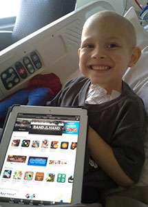 Child with cancer smiling with tablet
